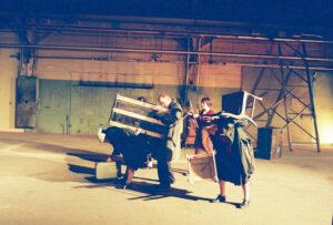 people lifting chairs - by Gülgün Kayim 2003