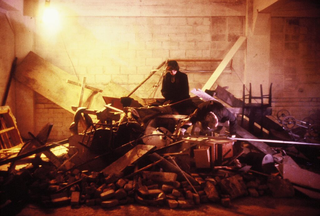 photo Untitled#1 - woman in chief beee over a pile of rubble