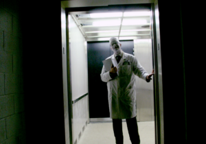 Strange Love 5 - man in white coat and face with white paint